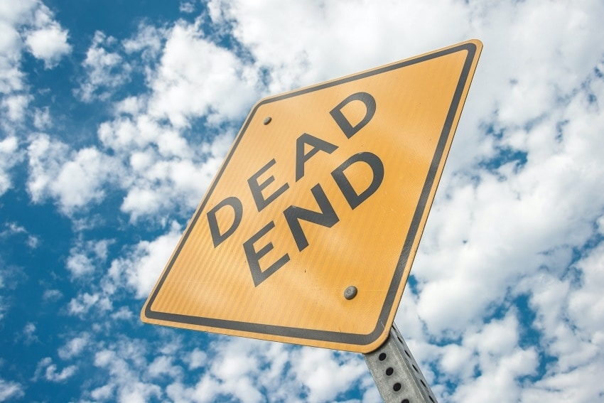 View of Street Sign Reading 'Dead End' from Below Against Cloudy Blue Sky
