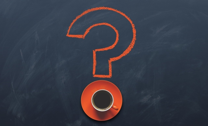 Orange question mark etched onto chalkboard surface, with orange saucer dot holding coffee mug
