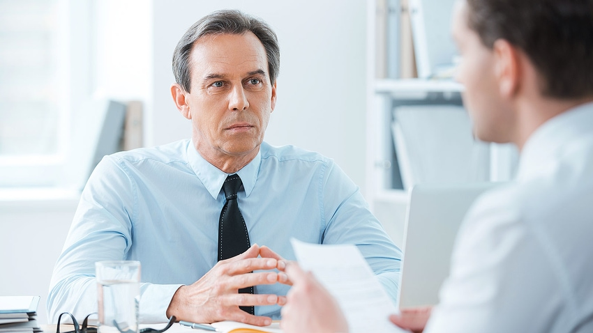 Frowning boss at desk looks skeptical during difficult discussion with employee about legal trouble
